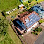 Luftaufnahme / Luftbild eines Hauses mit Solaranlage, Solarthermie und schönem Garten in Frühsommer
